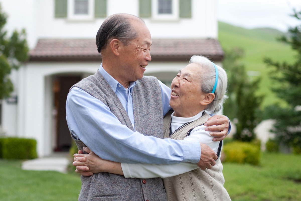 Two seniors hugging in front of house.