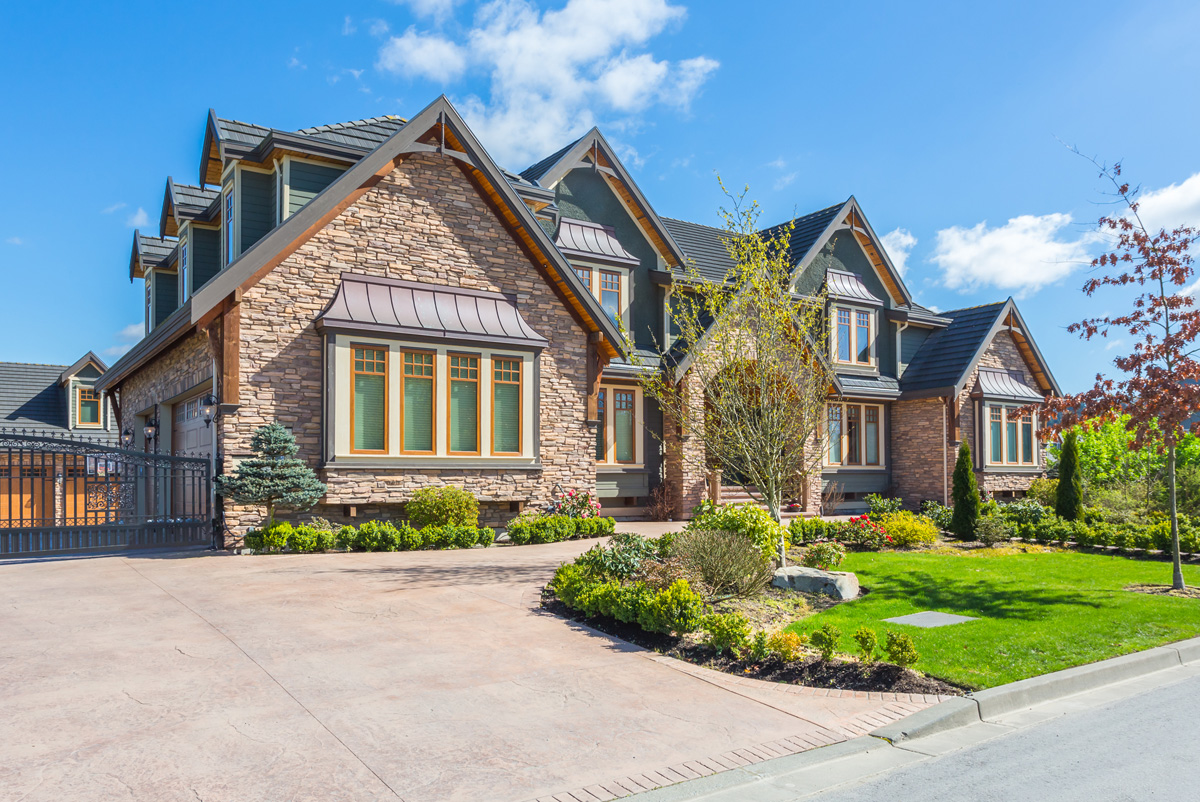 Large house with gated garage and beautiful landscaping.