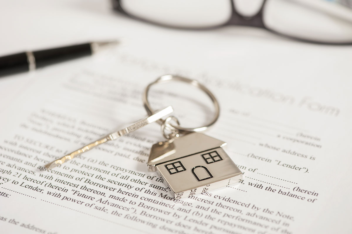 House key resting on mortgage agreement.